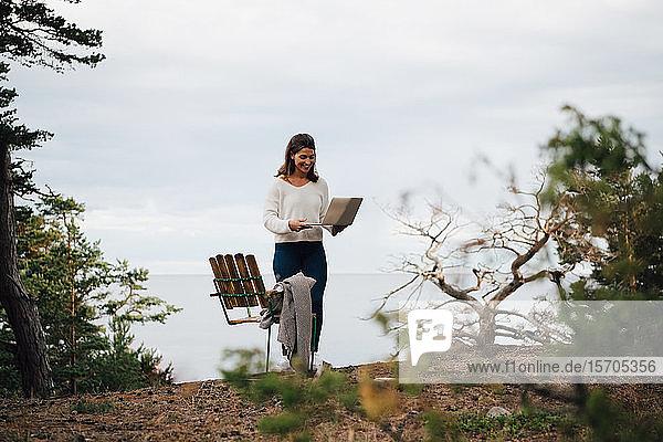 Lächelnde junge Frau mit Laptop  die an einem Stuhl im Wald gegen den Himmel steht