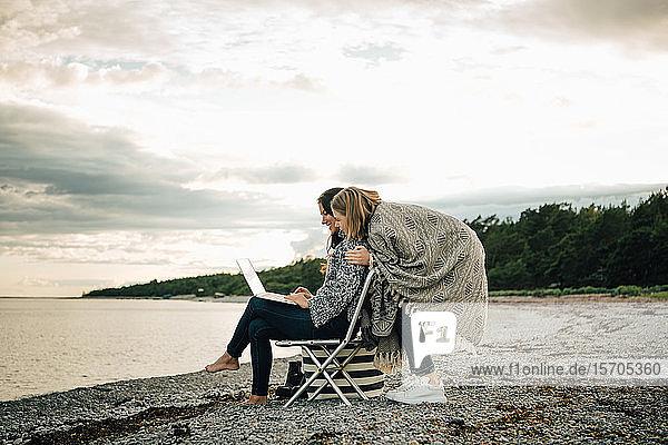 Freundin begrüßt Frau  die am Laptop arbeitet  während sie am Strand gegen den Himmel sitzt