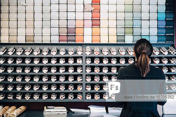 Rückansicht einer Frau bei der Auswahl von Tapeten und Farben  die im Laden zum Verkauf angeboten werden
