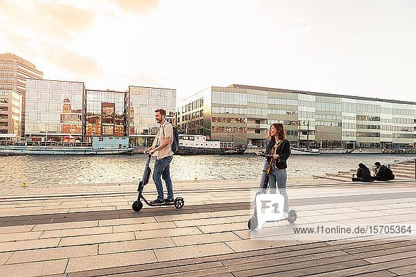 Glückliches Paar auf Elektro-Schieberollern auf der Promenade am Fluss in der Stadt gegen den Himmel
