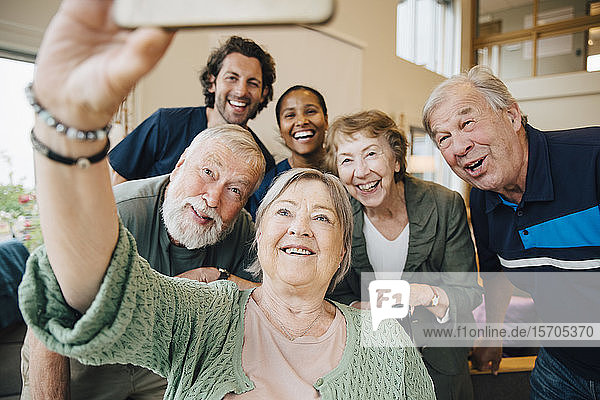 Senior woman taking selfie with friends and healthcare workers at retirement home