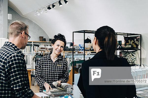 Lächelnde Verkäuferin zeigt dem Kunden im Geschäft ein Tapetenmuster