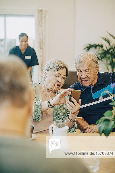 Ältere Frau teilt ein Smartphone mit einem Mann  während sie am Esstisch im Altenheim sitzt