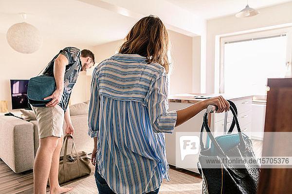Mittlerer Erwachsener Mann und Frau mit Gepäck in der Wohnung