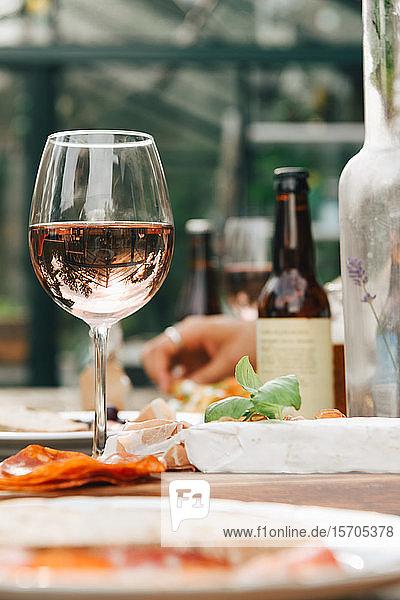 Nahaufnahme von Weinglas nach Essen auf dem Esstisch im Hof