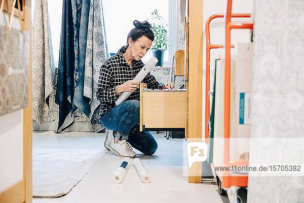 Verkäuferin in voller Länge beim Anordnen der Tapete in der Schublade