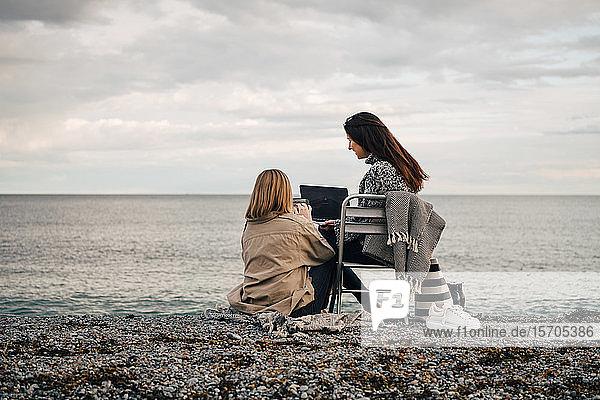 Freundinnen  die Technologien nutzen  während sie am Strand vor bewölktem Himmel sitzen