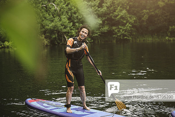 Portrait of smiling senior woman paddleboarding in sea during SUP course