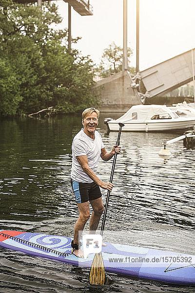 Porträt eines lächelnden älteren Mannes beim Paddeln auf See während eines SUP-Kurses