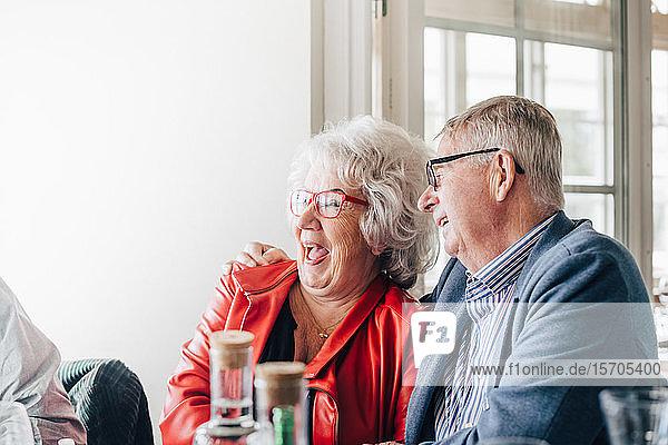 Ältere Frau im Gespräch mit männlichem Freund im Restaurant