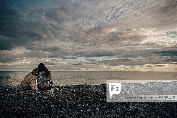 Rückansicht von liebenden Freunden  die am Meeresufer am Strand vor bewölktem Himmel sitzen