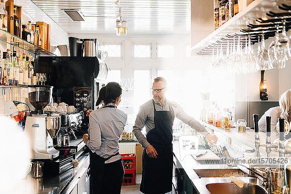 Männliche und weibliche Mitarbeiter  die in der Küche eines Restaurants arbeiten