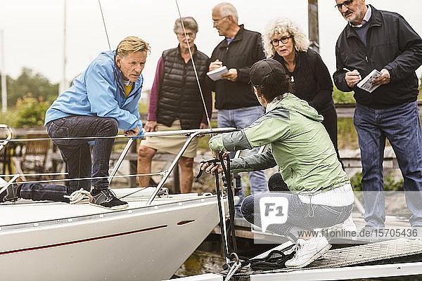 Ältere Männer und Frauen betrachten eine Ausbilderin  die ein Seil am Vertäuungsring am Pier bindet
