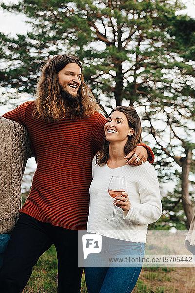 Glückliche Frau trinkt Wein  während sie mit einem lächelnden Freund im Freien spazieren geht