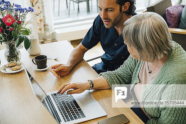 Zuversichtlicher männlicher Betreuer unterstützt ältere Frau beim Online-Shopping mit Kreditkarte und Laptop im Pflegeheim