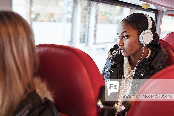 Nachdenkliches Teenager-Mädchen hört Musik über Kopfhörer  während es im Bus durch das Fenster schaut