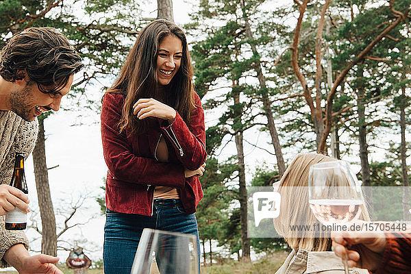 Fröhliche Frau unterhält sich mit Freunden bei einem Drink im Hinterhof