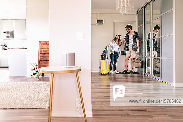 Full length of couple with luggage entering in apartment