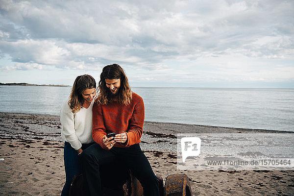 Lächelnder Mann zeigt der Frau sein Handy  während er am Strand sitzt