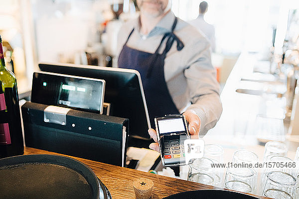 Midsection of man holding credit card reader in restaurant