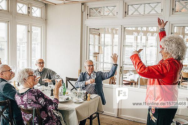 Ältere Frau gestikuliert  während männliche und weibliche Freunde im Restaurant sitzen