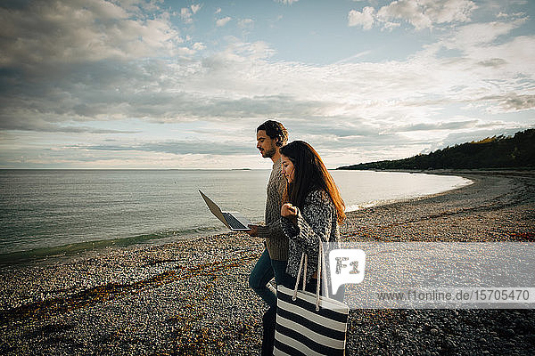 Woman walking with man using laptop on sea shore at beach against sky