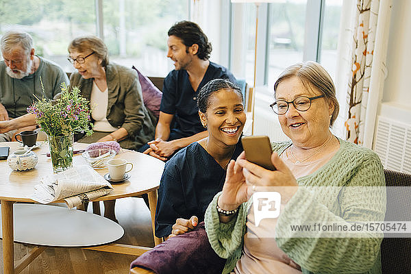 Pensionierte ältere Frau teilt ihr Smartphone mit lächelnder junger Krankenschwester beim Gemeindeeinsatz