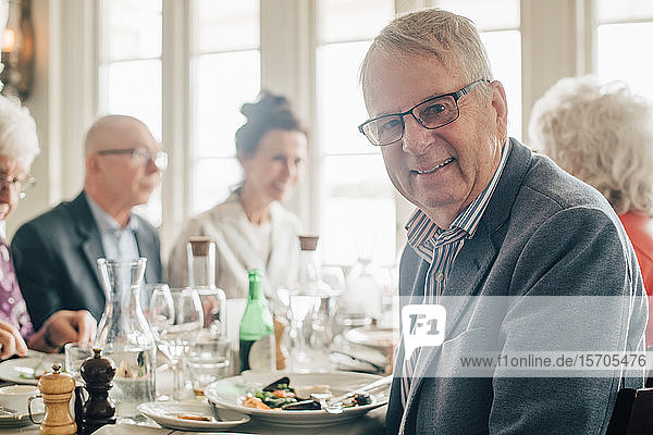 Portrait of senior man smiling while sitting by friends in restaurant
