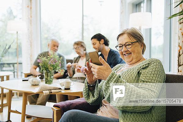 Lächelnde Rentnerin im Ruhestand benutzt Smartphone  während sie mit Freunden und Betreuer im Hintergrund auf einem Stuhl sitzt