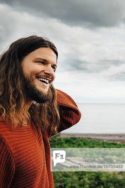Nahaufnahme eines lächelnden Mannes mit langen Haaren am Strand