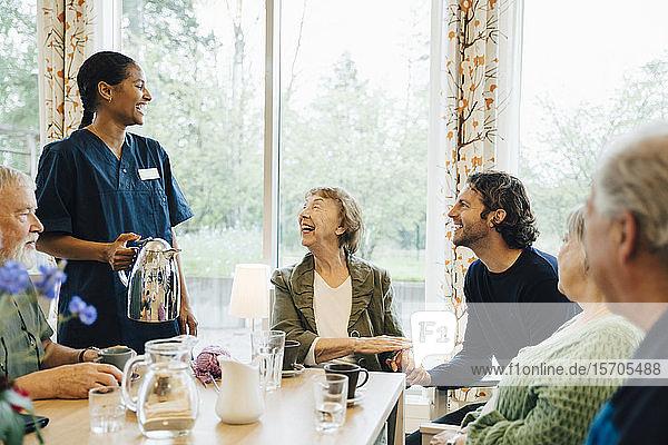 Fröhliche Krankenschwester im Gespräch mit älterer Frau  die mit Freunden und Enkel am Esstisch im Pflegeheim sitzt