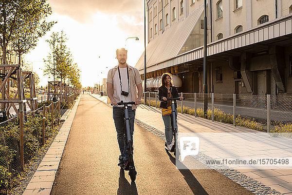 Mann und Frau fahren im Sommer auf Elektrorollern in der Stadt