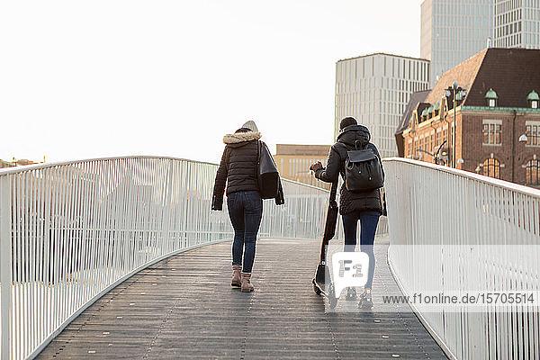 Rückansicht von Freundinnen  die mit einem E-Scooter auf einer Brücke in der Stadt laufen