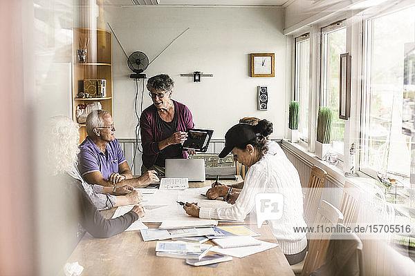 Weibliche Ausbilderin erklärt älteren Männern und Frauen während des Navigationskurses