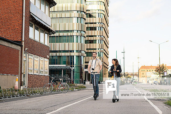 Ein glückliches Paar fährt auf Elektrorollern in voller Länge auf der Straße an Gebäuden in der Stadt vorbei