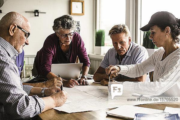 Ältere weibliche Ausbilderin erklärt älteren Männern und Frauen während des Navigationskurses über Karte