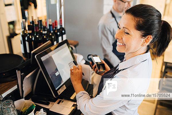 Lächelnde Frau benutzt Computer  während sie im Restaurant ein Kreditkartenlesegerät in der Hand hält