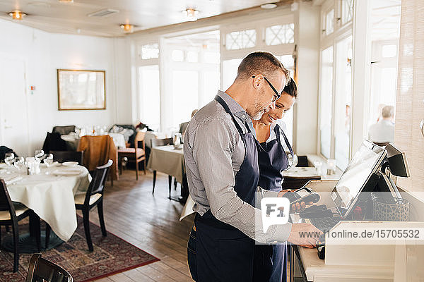 Smiling owners using computer while holding credit card reader in restaurant
