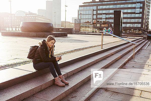 Teenager-Mädchen in voller Länge benutzt Mobiltelefon  während sie auf Stufen in der Stadt sitzt