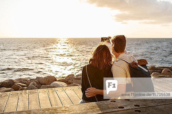 Rückansicht eines Paares  das sich mit einem Smartphone selbstständig macht  während es am Meer sitzt