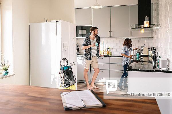 Mann trinkt Kaffee  während er eine in der Küche arbeitende Frau ansieht