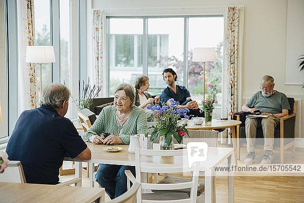 Ältere Männer und Frauen im Ruhestand  die mit einem Pfleger im Altenpflegeheim zusammensitzen