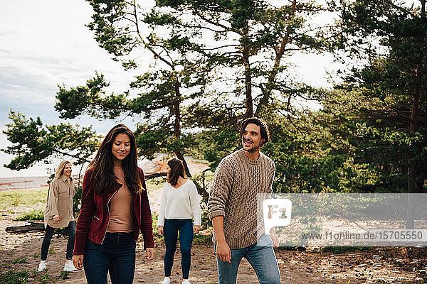 Lächelnde Freunde gehen im Wald gegen Bäume