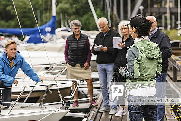 Weibliche Ausbilderin hält Seil  während sie älteren Männern und Frauen während des Bootsführerkurses Erklärungen gibt