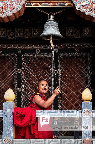 Buddhistischer Mönch beim Läuten der Gebetsglocke  Trongsa Dzong  Trongsa  Bhutan  Asien