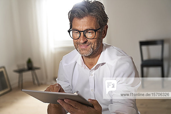 Portrait of smiling mature man wearing glasses using digital tablet at home