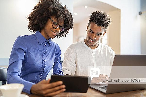 Schülerinnen und Schüler  die Laptop und Tablet für ein Projekt in einem Café benutzen