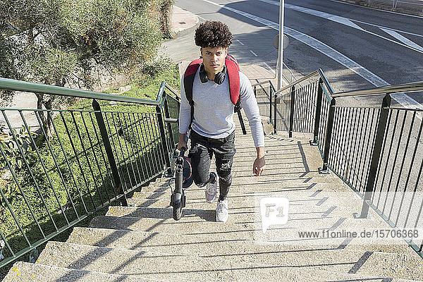 Junger Mann trägt E-Scooter auf Treppe