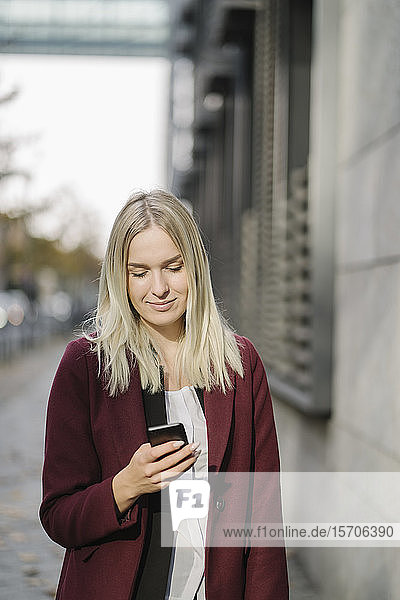 Blond businesswoman using smartphone in the city  looking down