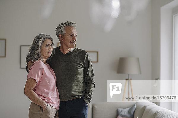 Älteres Ehepaar steht zu Hause im Wohnzimmer